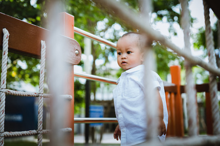 Asian boy playing in the playground in the park