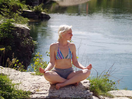 Woman meditating on the river beach photo