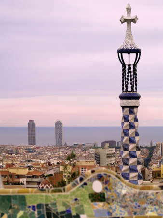 mediterranean sea:  the famous park Guell in barcelona at sunset - the city skyline and the mediterranean sea in the background
