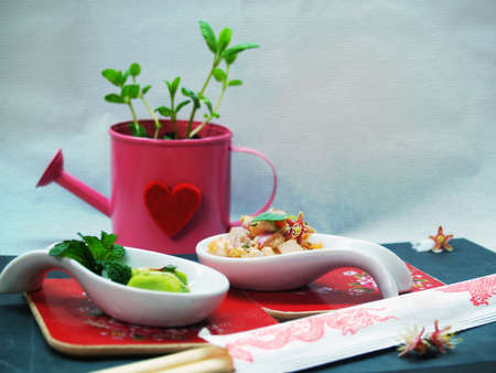 Asian style composition with a watering can and with salmon tartare and wasabi in a white spoon photo