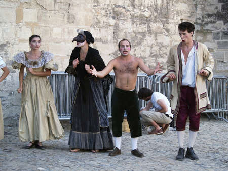 Avignon, France - July 30th, 2005: troupe of actors in historical costumes advertising their performance on place in front od Palais des Papes