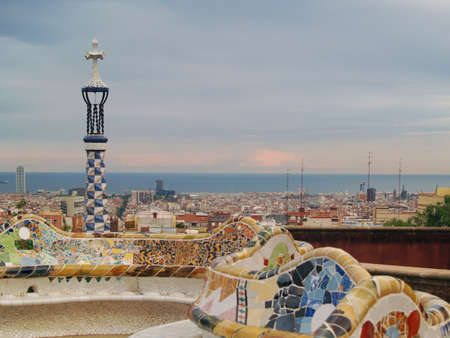 the famous park Guell in barcelona at sunset - the city skyline and the mediterranean sea in the background