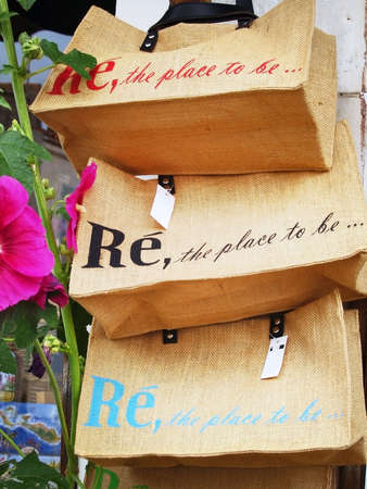 Ile de Re (Island of Re): Shopping bags in a souvenir shop with a Hollyhock flower on foreground (typical of the island)  in France, Atlantic ocean.