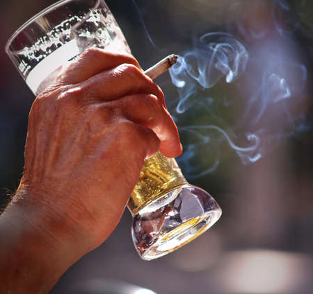 un vieil homme assis � la table de pub pour la bi�re potable en plein air et le tabagisme