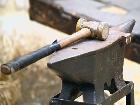 medieval blacksmith: Old anvil with hammer on a metal stump  Stock Photo