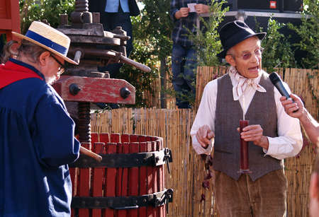 jus: Chusclan village, France - October, 13th, 2012: an old man holding a glass of grape jus explaining traditional winemaking process using manual grape crushing machine during 14th festival grape harvest of the history, Chusclan, France.