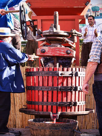 winepress: Chusclan village, France - October, 13th, 2012:  traditional Wine Pressing using a manual grape crushing machine during 14th festival grape harvest of the history, Chusclan, France.