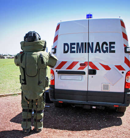 Young male soldier in bomb suit behind bomb squad vehicle used by military to difuse and disarm explosive bombs. photo