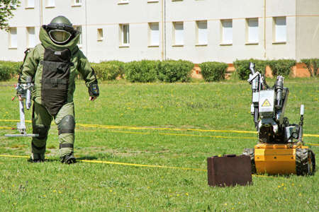 Young male soldier in bomb suit with a  bomb squad robot used by military to difuse and disarm explosive bombs.