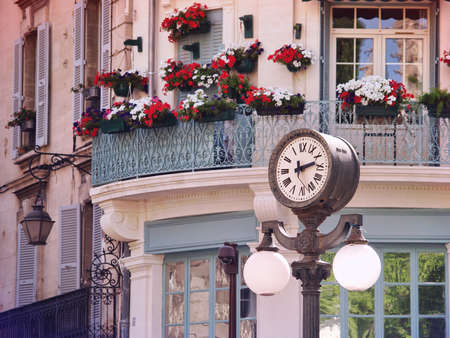 Scene with a historic clock in Old center of Avignon, France, Provence
