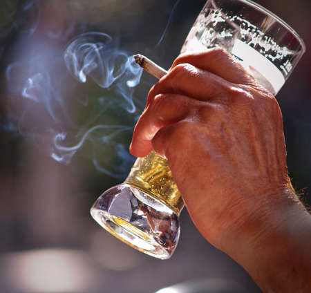 an old man sitting at the table in outdoor pub Drinking beer and smoking Stock Photo