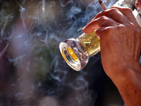 man smoking: un anciano sentado a la mesa en la cerveza al aire libre Beber y fumar pub