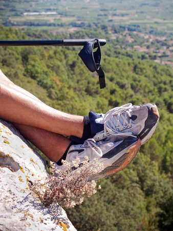 men s boot: hiker sitting near the cliff
