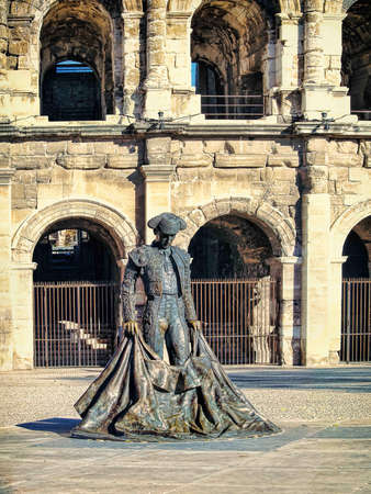 Roman Coliseum with a statue of a bullfighter- Nimes, France photo