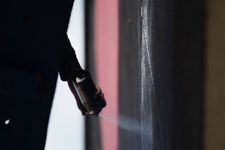 sprayed: the process of creating graffiti is sprayed paint on the wall of the building from a container
