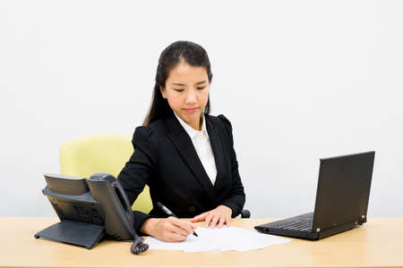 Thai business woman writing a document photo
