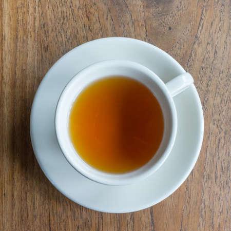 overhead shot: Tea cup on a wood table