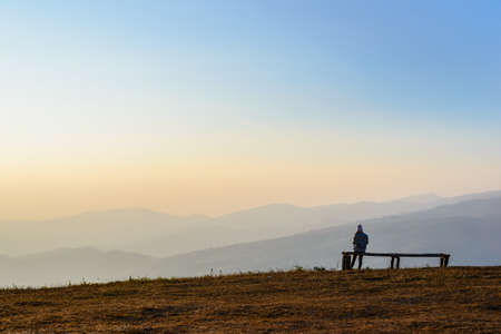 People sitting on a bench enjoy the scenery view of mountain and blue sky Banco de Imagens
