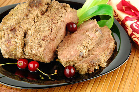Succulent roast beef meat slices with cherry on a black plate photo