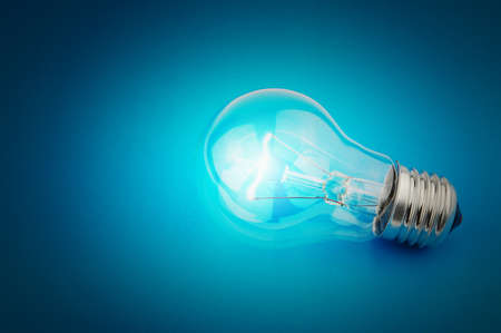 glowing light bulb: Electric light bulb on a blue background