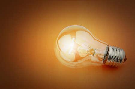 bombilla: Bombilla de luz el�ctrica sobre un fondo naranja Foto de archivo