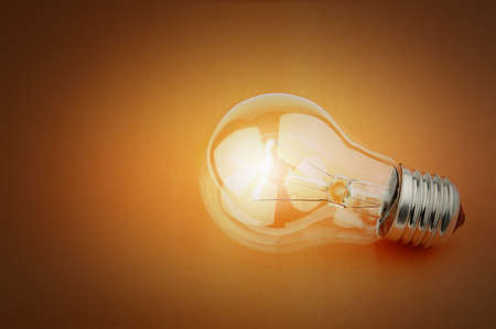 glowing light bulb: Electric light bulb on a orange background