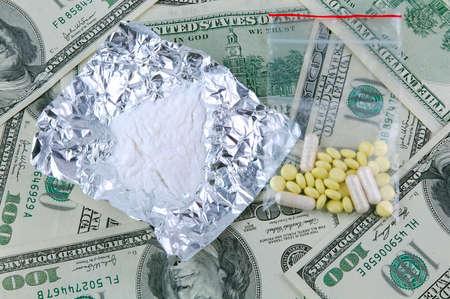 sobredosis: Drogas sobre un fondo de billetes de dólar americano