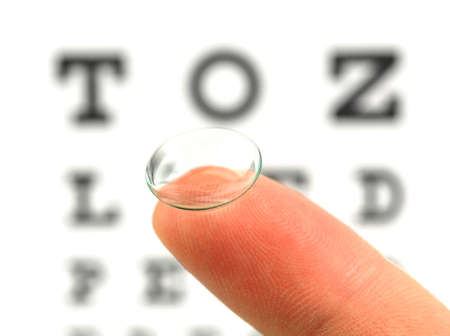 Contact lens on finger and snellen eye chart. The eye test chart is shown blurred in the background. Stock Photo