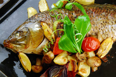 Baked fish with vegetables, mushrooms and lemon.