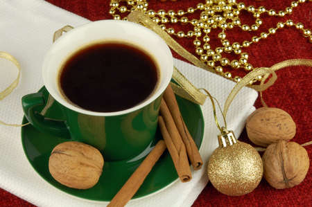 Coffee cup with cinnamon, walnuts and christams decoration photo