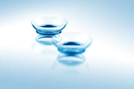 Two contact lenses with reflections on blue surfaces. Focus on long-distance lens.