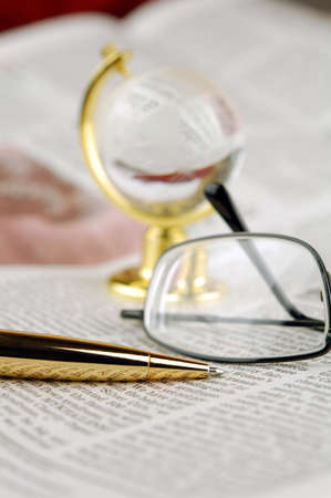 Glasses, pen, globe lie on a newspaper  photo