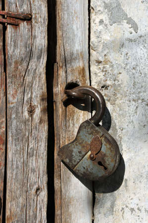Rusted open padlock on the old wooden door Stock Photo - 16211807