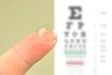 Contact lens on finger and snellen eye chart  The eye test chart is shown blurred in the background  Stock Photo
