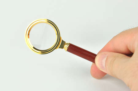 Magnifying glass in male hand on gray background Stock Photo - 16452399