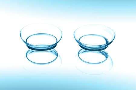 contact lenses: Dos lentes de contacto con la reflexi�n sobre fondo azul