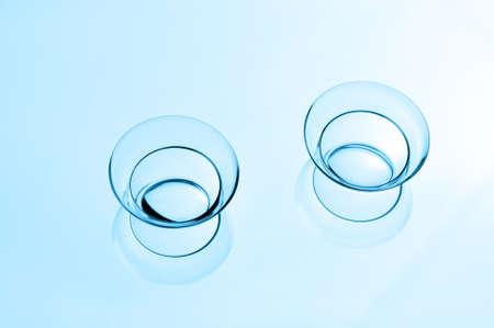 lentes contacto: Dos lentes de contacto con reflexiones sobre un fondo azul. Foto de archivo
