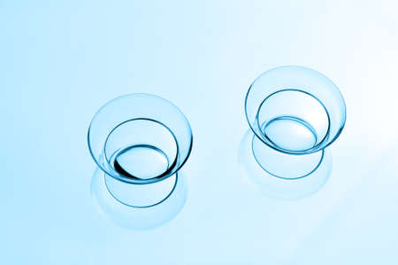 Two contact lenses with reflections on a blue background.