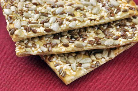 Flaky pastry cookies with seeds: sunflower, sesame and flax. Closeup with extremely shallow dof.