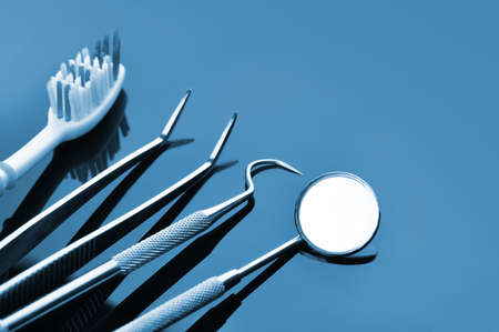 Dental care. Dental tools on a blue mirrored background. Dental treatment.