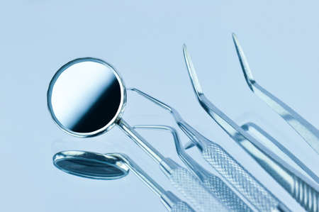 Dental tools on a blue background with reflection. Dentistry concept.