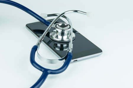 Stethoscope on the smartphone on a grey background. Phone repair and service concept. Concept a health of device.