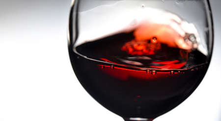 Red wine on grey background, abstract splashing. Copy space for your text. Closeup.