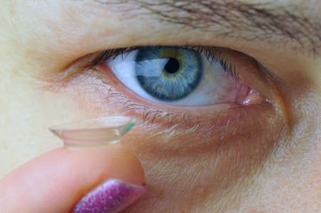 Woman holding contact lens near her eye. Closeup image. Focus on eye. 版權商用圖片