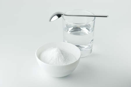 Baking soda, spoon and glass of water. 免版税图像