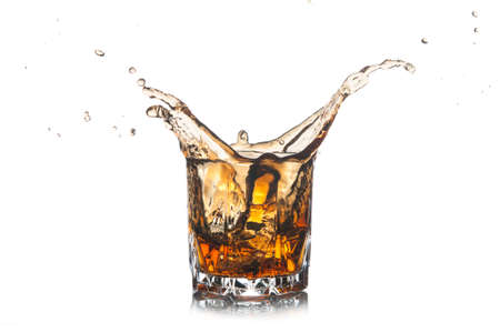Whiskey splash out of glass isolated on white background.