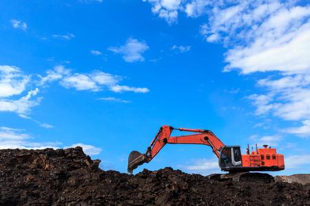 maquinaria pesada: Backhole y carbón en el cielo azul Foto de archivo