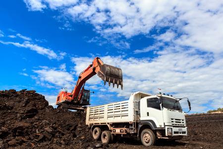 camion minero: Backhole y carbón en el cielo azul Foto de archivo