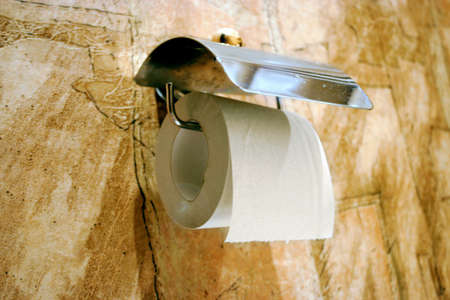 toilet paper in holder on background wall with abstract background photo
