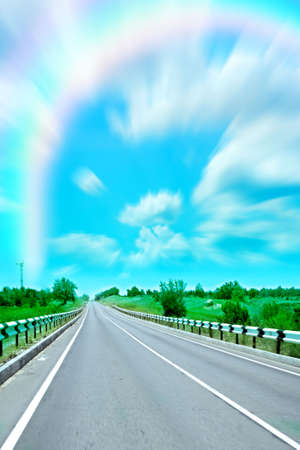 colorful cloudscape: varicoloured rainbow on blue sky on road by landscape